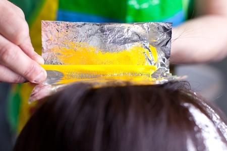 tinte cabello: Primer plano de una peluquería de envolver el pelo de color en papel de aluminio aluminimum. Enfoque selectivo. Foto de archivo