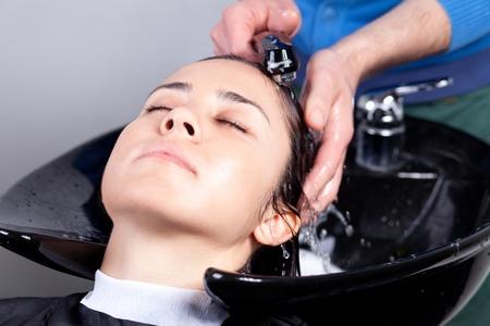 Haidresser washing womans hair at a hair salon. Selective focus. photo
