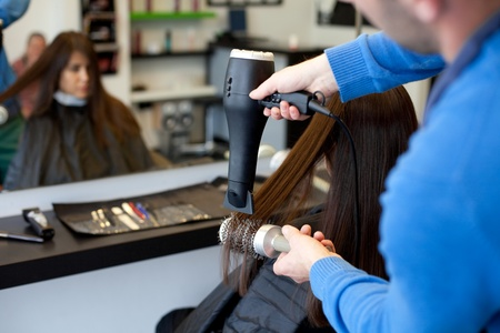 dryer: Hairdresser drying womans hair using hair dryer and round brush. Selective focus.