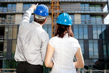 Construction engineer pointing on an area of the building on construction site photo