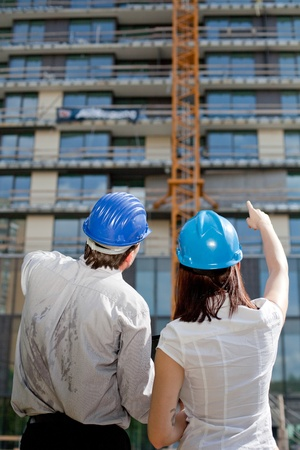 Female construction engineer pointing on a building at construction site. Selective focus. Stock Photo - 13493574