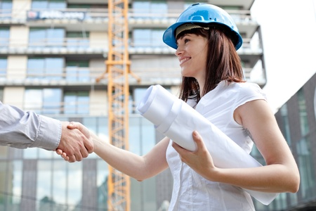 Young female construction engineer shaking hands at construction site photo