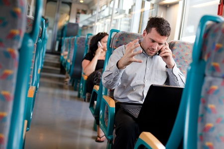 Businessman receiving bad news on a train photo