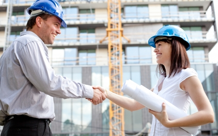 female architect: Construction engineers shaking hands at the construction site. Selective focus. Stock Photo