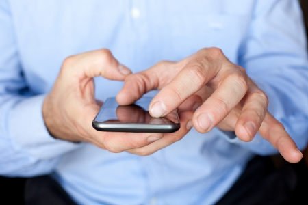 zoom in: Close up view of a businessman using multi gestures on a smartphone to zoom in a document