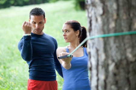 outdoor training: Perosonal trainer working with his client, showing her how to properly execute the exercise with resistance band