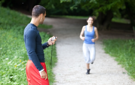 personal trainer woman: Personal trainer timing a female runner  Selective focus  Stock Photo