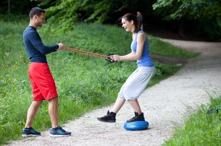Personal trainer working with a young woman, balance exercise photo