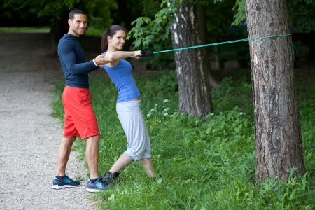 elastic: Personal trainer working with his client  Resistance band exercise  Stock Photo