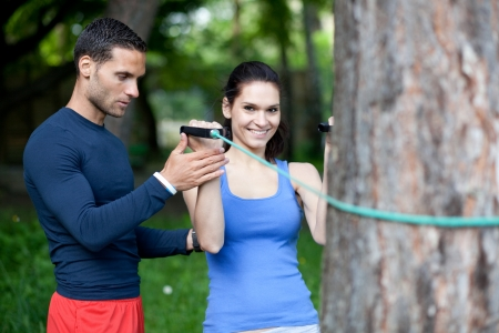 elastic band: Personal trainer showing his client how to properly execute biceps exercise with resistance band