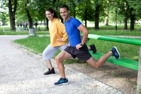 outdoor training: Happy young couple exercising outdoors, using a park bench to do a leg exercise Stock Photo