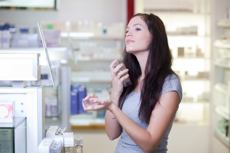 Young woman buying perfume in a beauty store photo