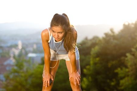 sudando: Montar una mujer joven que tiene un descanso durante el entrenamiento