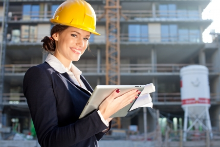 Female construction engineer / architect with a tablet computer at a construction site photo