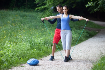 outdoor training: Personal trainer working with his client, helping her with execution of shoulder exercise Stock Photo