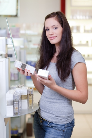 Young woman looking for a perfume in a beauty store photo