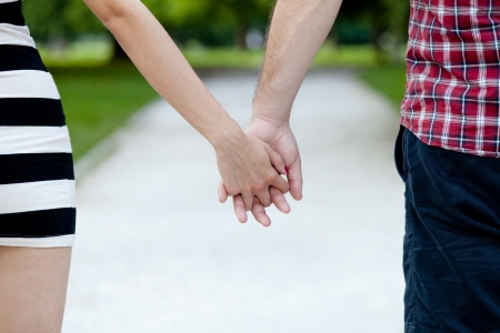 Close up view of a young couple holding hands photo