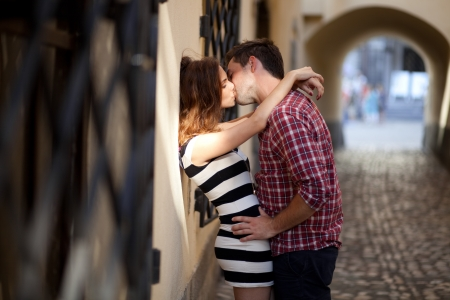 Young couple in love, kissing in the old part of town photo
