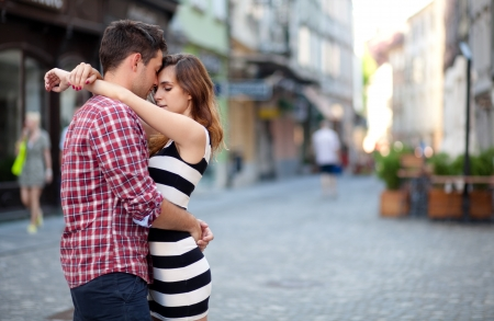 romantic kiss: Young couple in love, hugging on the street