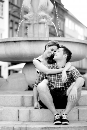 Affectionate young couple sitting by the fountain photo