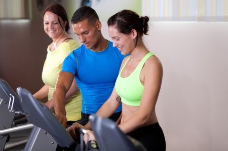 Personal trainer setting treadmill for a couple of young women photo