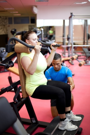 Personal trainer showing a woman how to properly execute a leg exercise photo