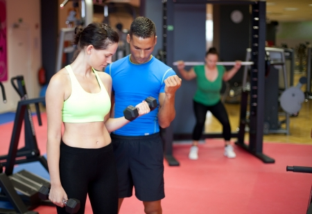 Personal trainer showing a young woman a bicep exercise photo