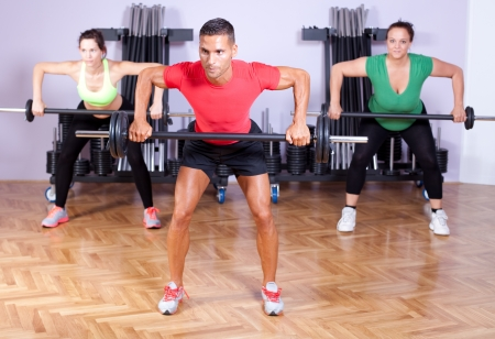 A group of young people in aerobics class doing a dead lift exercise photo