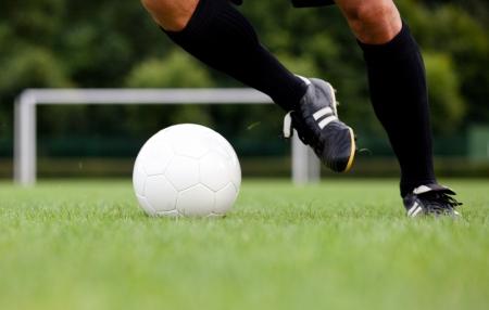 cancha de futbol: Vista detallada de un jugador de fútbol  jugador de fútbol botando el balón. Enfoque selectivo.