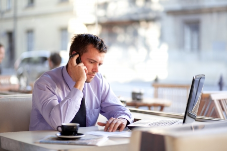 serious businessman: Authentic image of a businessman working in a coffee shop Stock Photo