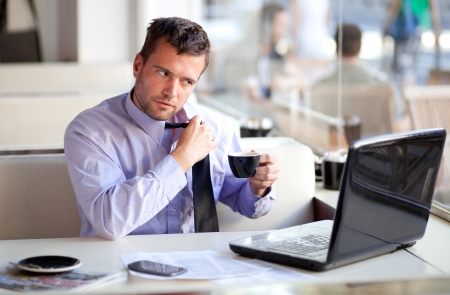 Overworked businessman untying his tie in a cafe Stock Photo - 15141322