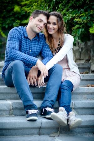 jovenes enamorados: Pareja joven sentado en las escaleras y tomados de la mano Foto de archivo