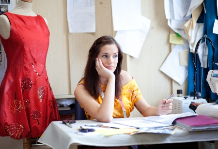 Fashion designer daydreaming in her studio Stock Photo - 15690040