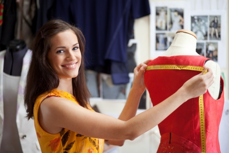 tailor measuring tape: Fashion designer measuring a dress. Shallow depth of field. Stock Photo