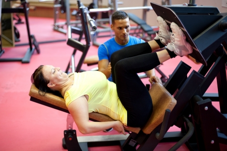 personal trainer woman: Woman doing leg exercise under personal trainers supervision. At the gym. Stock Photo