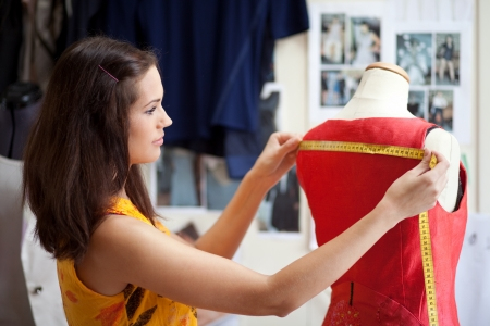 designed: Fashion designer measuring a dress. Shallow depth of field. Stock Photo