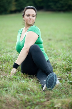 Plus sized woman stretching in the park. Selective focus. photo