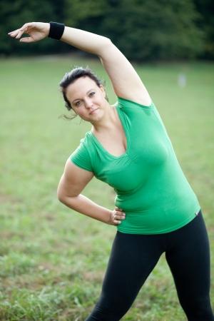 regordete: Mujer con sobrepeso que estira en el parque