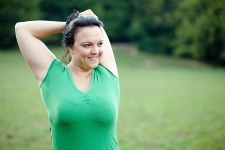 Overweight woman stretching in the park. Selective focus.