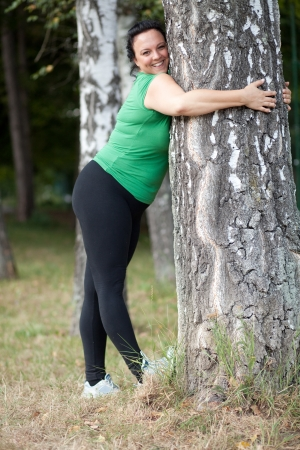 chubby girl: Happy plus sized woman stretching and hugging a tree