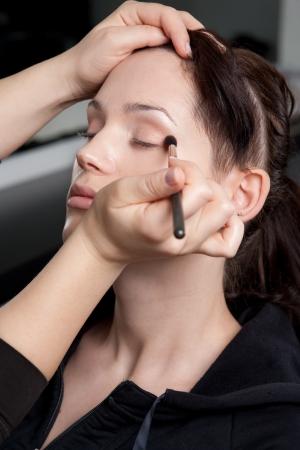 applicator: Professional make up artist applying make up to a fashion modelbride. Stock Photo