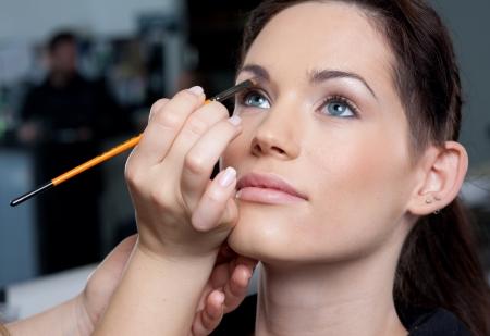 bridal makeup: Make up artist applying make up to a fashion modelbride Stock Photo