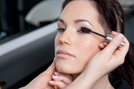 make up artist: Make up artist applying mascara to a fashion modelbride