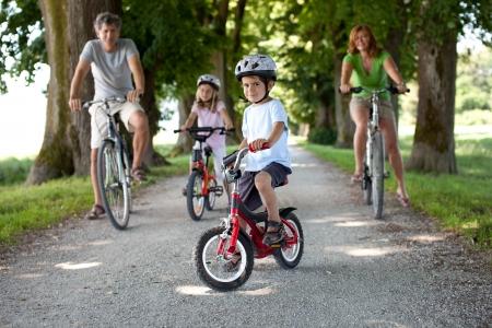 ni�os en bicicleta: Muchacho de 4 a�os sentado en su bicicleta delante de su familia