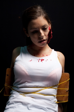 Kidnapped and tortured young woman with a big cut on her face, tied up Stock Photo