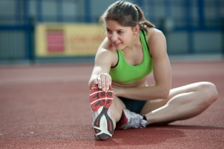 jogging track: Professional female sprinter stretching before training. Selective focus. Stock Photo