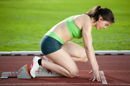 sprinting: Sprinter in the starting blocks, getting ready to go Stock Photo