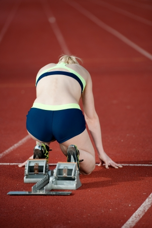 flexed: Female sprinter in starting blocks getting ready to go Stock Photo