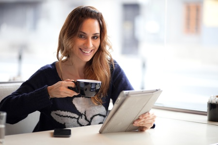 cafe internet: Feliz joven mujer bebiendo caf�  t� y usa la tableta del ordenador en una tienda de caf� Foto de archivo