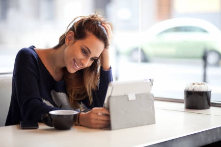 Candid image of a young woman using tablet computer in a coffee shop photo